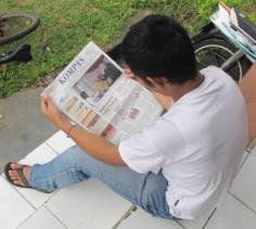 Beim Kompas lesen vor dem Büro in Curup