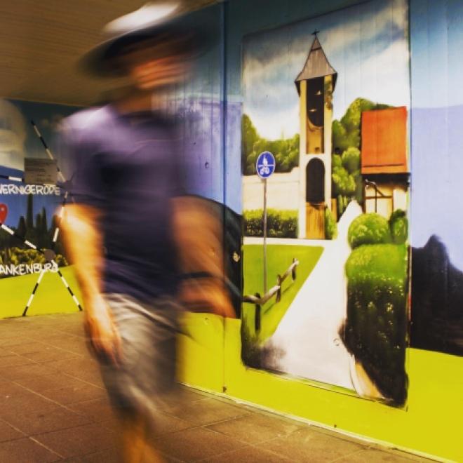 Passant läuft im Bahnhof Wernigerode, Unterführung, an einem gesprühten Bild vorbei. Foto Andre Eberle